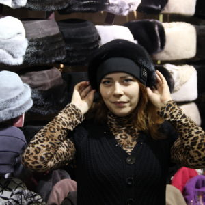 Женщина выбирает шапки