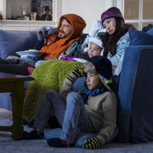 Семья в верхней одежде сидит в неотапливаемой гостинной