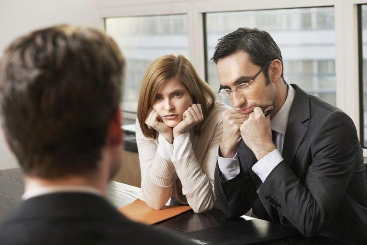 Мужчина и женщина сидят за столом и слушают собеседника