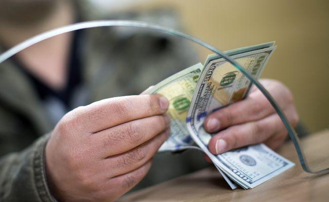 Мужчина пересчитывает доллары на кассе