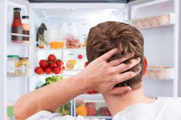 Парень держится за голову, смотря в холодильник