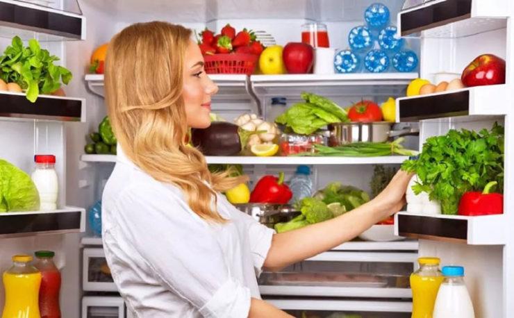 Девушка рассматривает продукты в холодильнике