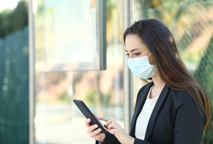 Девушка в маске и смартфоном в руке