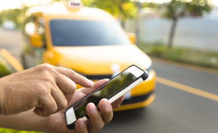 Смартфон в руках на фоне такси