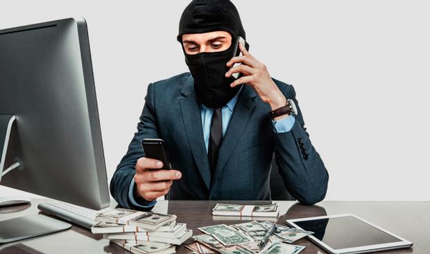 Мужчина в балаклаве говорит по телефону за рабочим столом