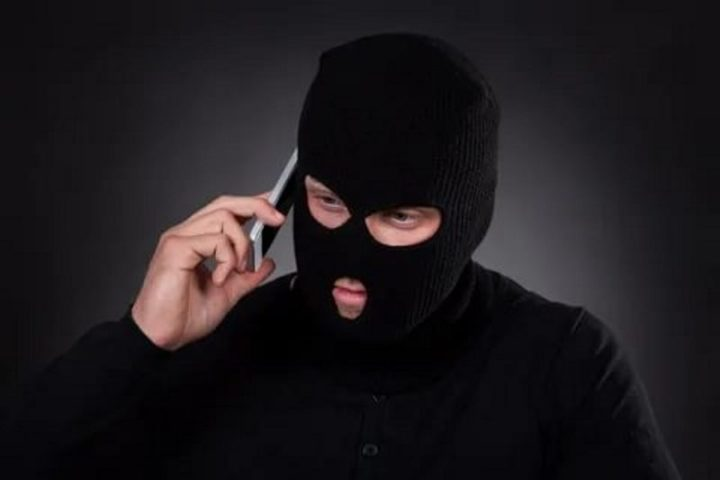 Мужчина в балаклаве говорит по телефону