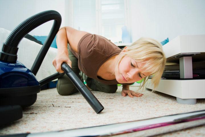 Девушка вычищает ковер пылесосом без насадки