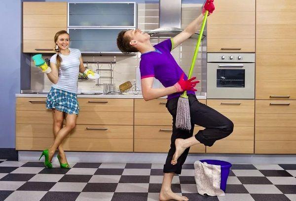 Девушка смеется, парень играет на швабре