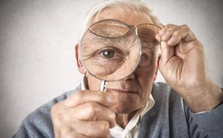Пожилой мужчина смотрит в увеличительное стекло