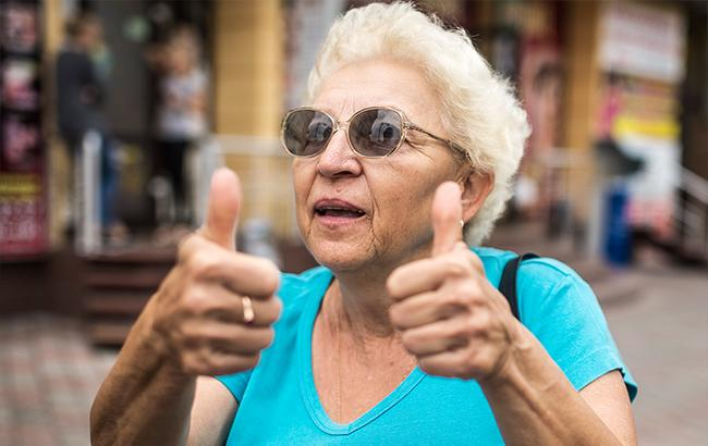 Пожилая женщина держит пальцы вверх