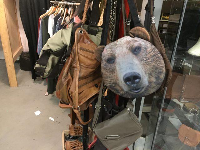Сумки и медвежья морда на вешалке в магазине