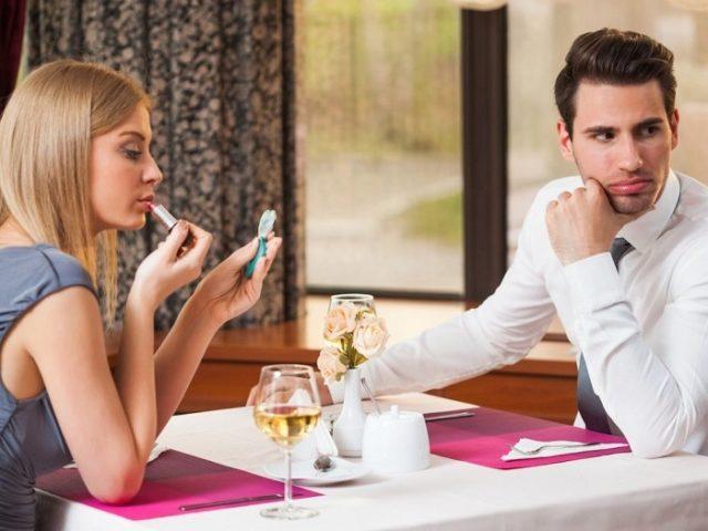 Девушка красит губы за столом, а парень смотрит в сторону