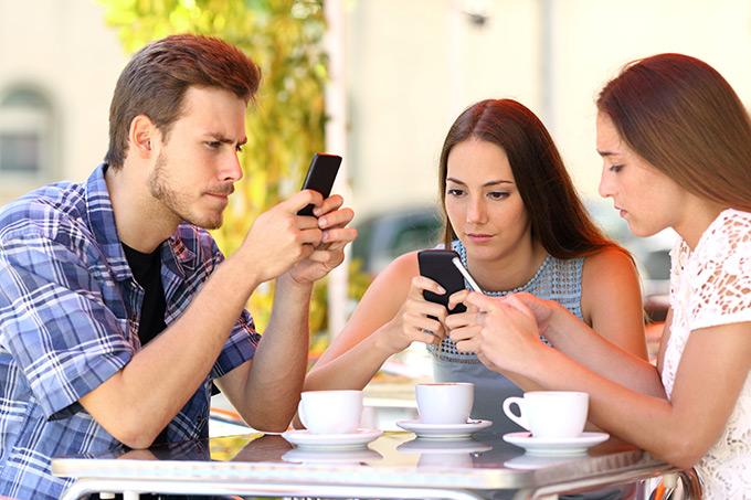 Молодые люди используют гаджеты за столом