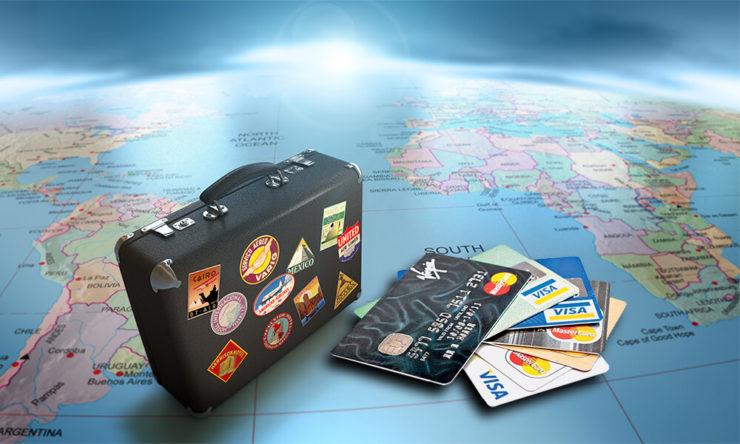 Чемодан, банковские карты и карта мира