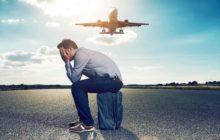 Человек сидит на чемодане на фоне взлетающего самолета