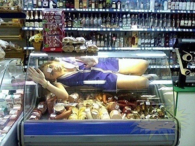 Продавщица в витрине с продуктами