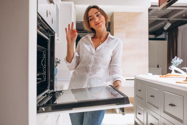 Девушка на кухне смотрит в духовку