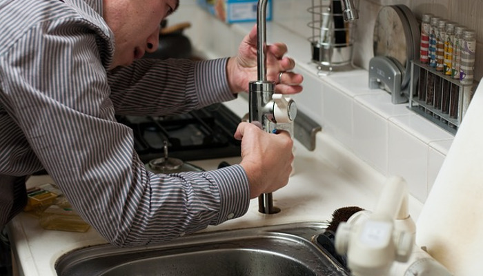 Мужчина пытается починить кран