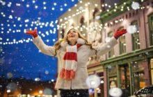 Девушка на украшенной улице радуется новогодней атмосфере