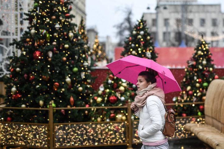 Девушка под розовым зонтом на красиво украшенной к Новому году улице