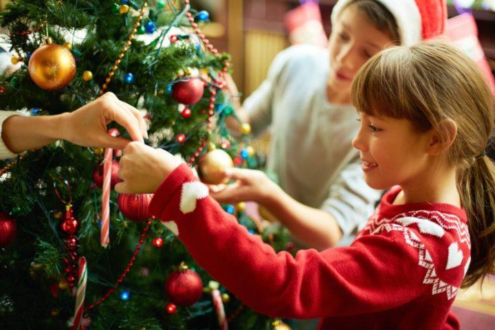 Девочка на переднем фоне и мальчик на заднем украшают новогоднее дерево