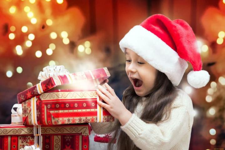 Девочка в шапке Санты распаковывает подарки