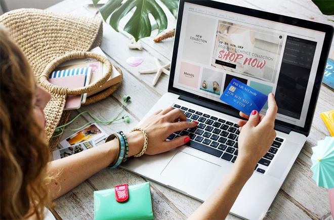 Девушка возле ноутбука с банковской картой в руках