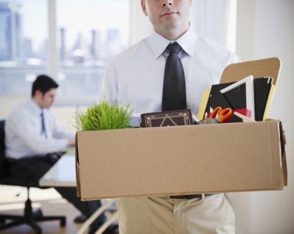 Сотрудник уходит с рабочего места с коробкой с вещами