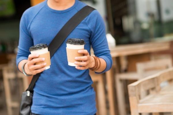 Парень держит в руках два стаканчика кофе