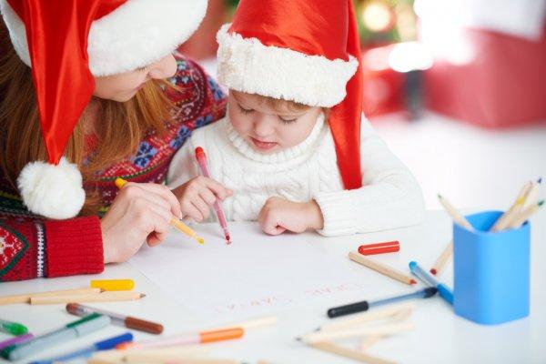 Мама и ребенок в шапках Санты пишут письма Деду Морозу