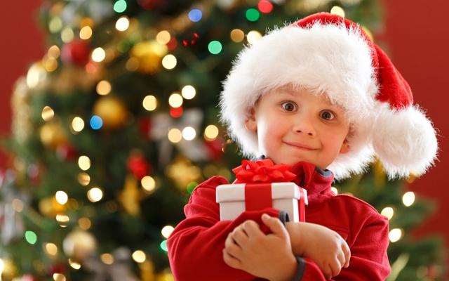 Малыш в шапке Санты на фоне новогодней елки