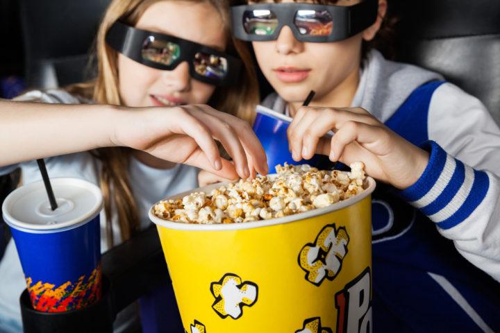 Дети в 3D-очках едят попкорн в кинотеатре