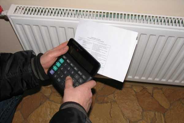 Мужские руки держат калькулятор и платежные квитанции на фоне радиатора