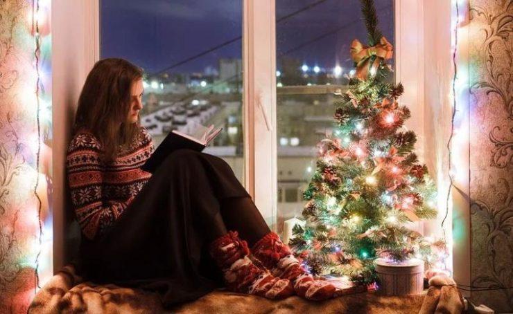 Девушка сидит на подоконнике нс книгой и новогодней елочкой
