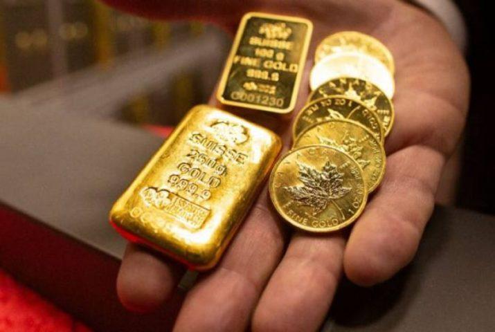 Золотые слитки и монеты в руке