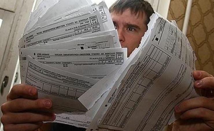 Мужчина рассматривает квитанции на коммуналку