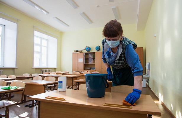 Уборщица вытирает парту в школьном классе
