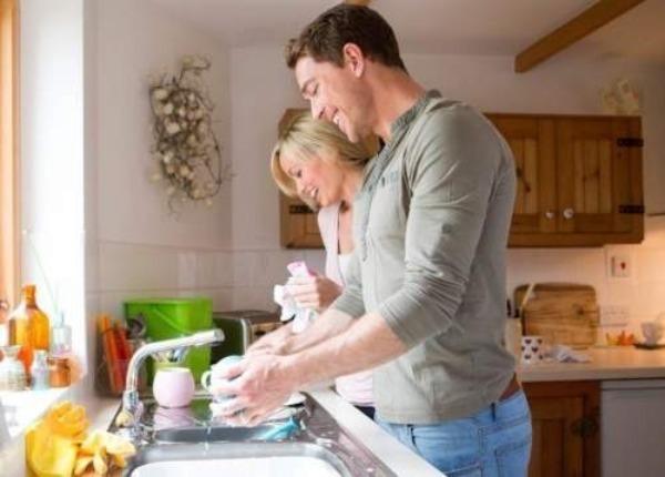 Пара с улыбкой моет посуду