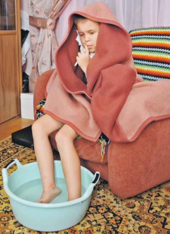 Мальчик парит ноги в тазике с водой