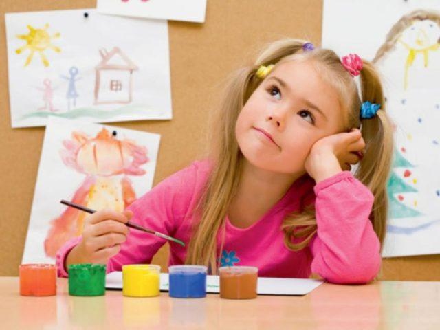 Девочка задумалась во время рисования