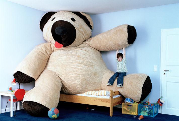 Гигантский игрушечный медведь и мальчик в детской