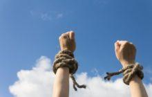 Руки на фоне неба с разорванными веревками на запястье
