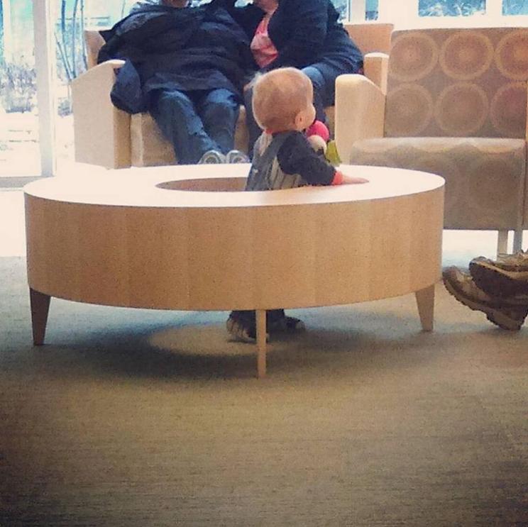 Ребенок в столе, а взрослые на диване
