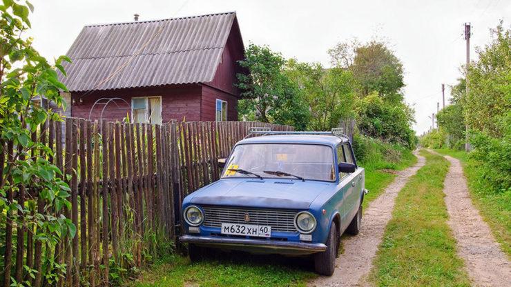 Автомобиль, припаркованный под покосившимся дачным забором
