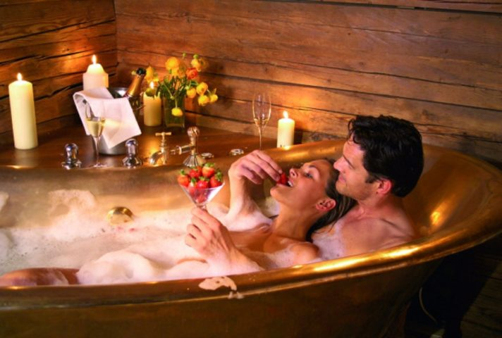 Пара принимает ванну и ест клубнику