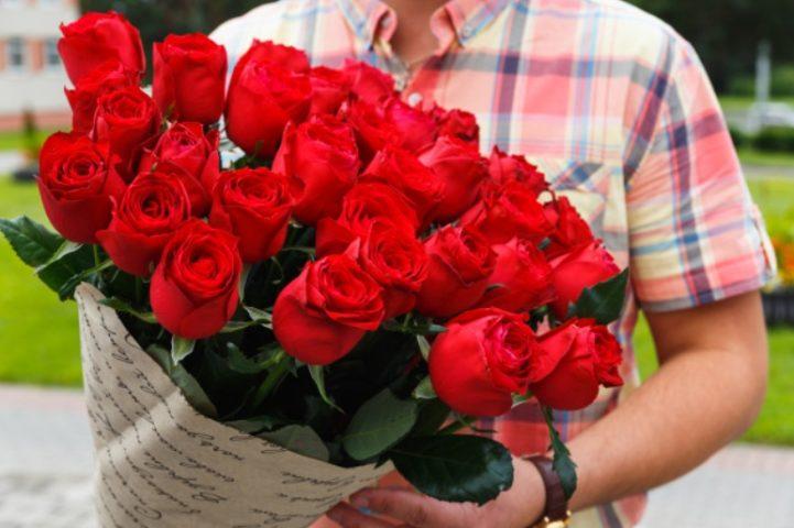 Большой букет красных роз в мужских руках