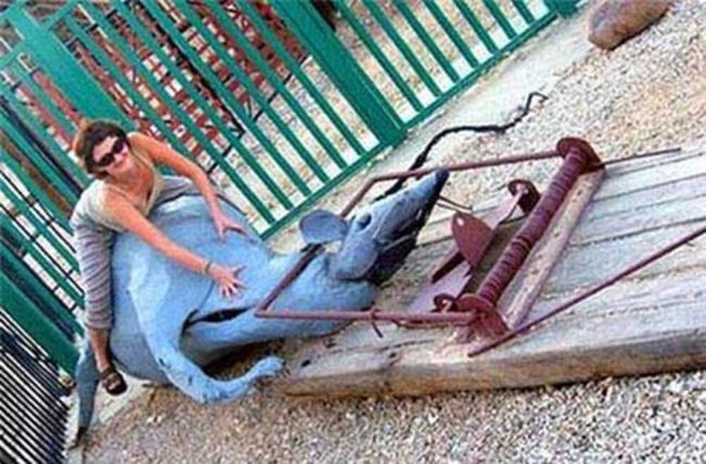 Женщина сидит на инсталляции в виде попавшей в мышеловку мыши