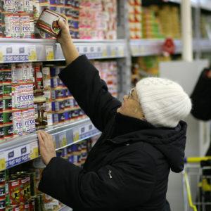 Женщина выбирает тушенку в супермаркете