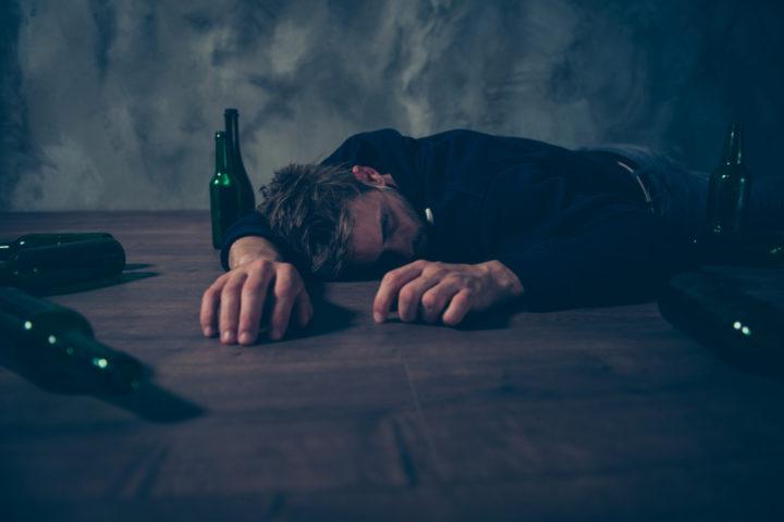 Пьяный мужчина лежит на столе в окружении пустых бутылок