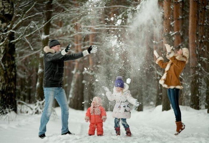 Семья на улице играет снегом